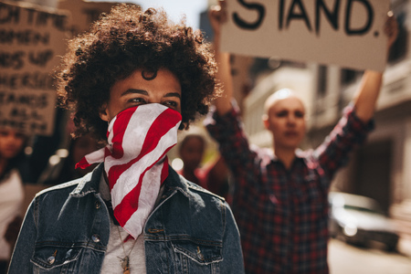 Portrait of silent protesting young woman with group in background. African female covering her mouth with a scarf and protesting on road with group of female activists. Stock Photo