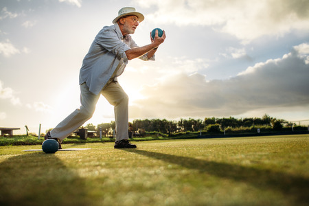 Low angle view of a senior man in position to throw a boule. Old man playing boules in a lawn with sun in the background. Stock Photo