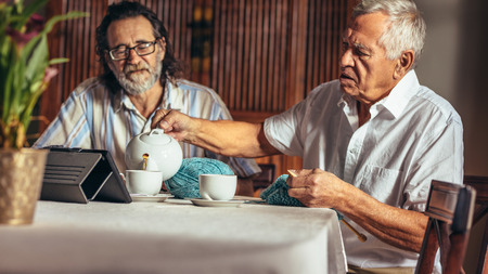 Senior men sitting at home having tea while knitting. Elderly man pouring tea from teapot in cups with a friend sitting by. 스톡 콘텐츠