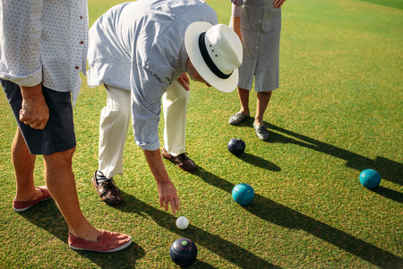 Senior man in hat bending down to pick a boules in a lawn. Elderly man playing boules in a lawn with his friends.