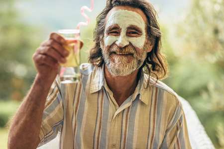 Bearded senior man with clay facial mask holding a glass of juice in hand. Man having spa facial treatment raising his juice glass at camera.