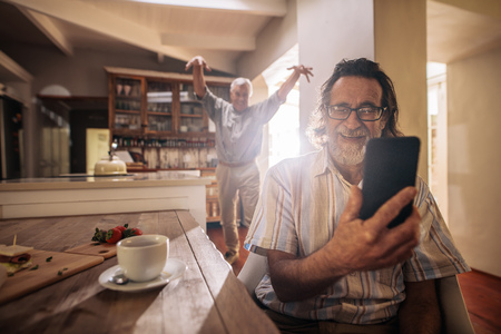 Happy senior man taking selfie with friend standing at back making funny gestures.  Two elderly men taking selfie with mobile phone at home.