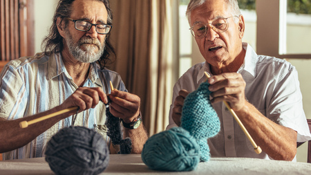 Two senior friends knitting at home. Elderly men making warm clothes with needles and wool yarn. 스톡 콘텐츠