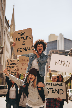 Group of young female activist protesting with signboards on road. Women enjoying during a demonstration on road. Reklamní fotografie - 116932159