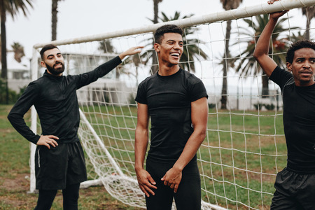 Three footballers standing at the goalpost taking a break during a football match. Stock Photo