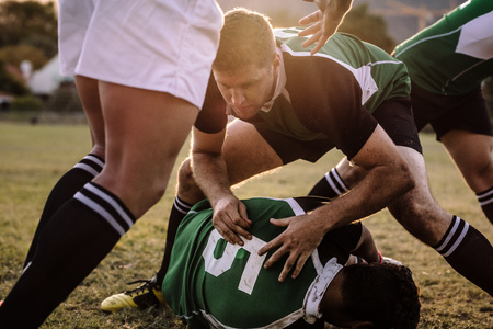 Rugby players fighting to get the ball during the match.