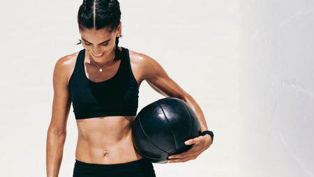Portrait of a fitness woman standing holding a medicine ball.