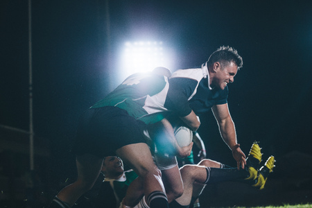 Rugby players in uniform giving a tackle on stadium. Rugby player trying to block the opponent and get the ball under lights.