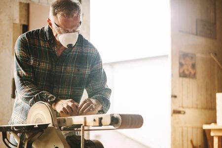 Senior carpenter with mask using belt sander. Banque d'images - 116932472