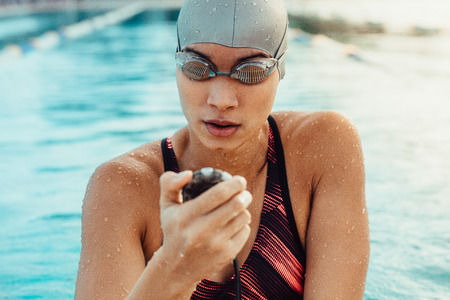Female swimmer checking a stopwatch after a lap. Zdjęcie Seryjne