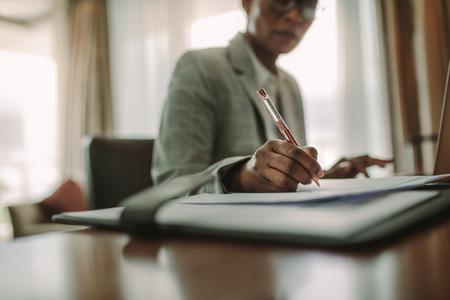 Businesswoman sitting at hotel room desk writing on document. 版權商用圖片