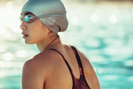 Close up of fit young female swimmer in swim cap and goggles looking away.