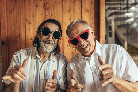 Senior men wearing funny sunglasses looking at camera. Happy elderly friends with crazy eyewear with funky gestures. 스톡 콘텐츠