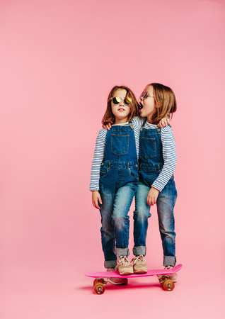 Twin girls wearing fashion clothes with skateboard on pink Фото со стока