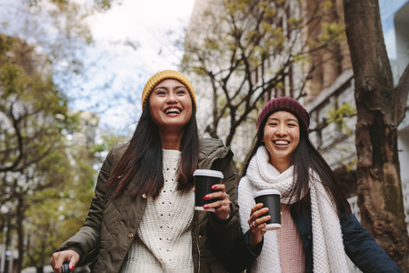 Smiling women in winter wear walking on street drinking coffee.