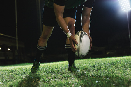 Rugby player dropping the ball to the ground for kicking as it touches the ground.