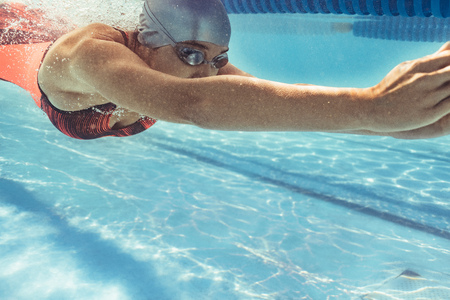 Underwater shot of female swimmer swimming in pool.