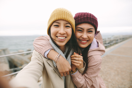 Cheerful asian woman in winter wear standing near the sea on a cold morning. Stock Photo