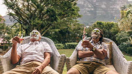 Elderly men with facial mask and cucumber slices on their face at spa. 스톡 콘텐츠