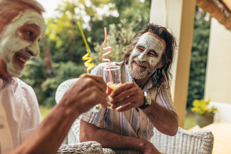 Happy old people toasting juice glasses with facial clay mask on.