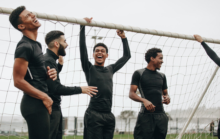 Soccer players standing near the goalpost relaxing and laughing.