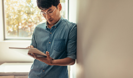 Asian man leaning to a wall and using digital tablet. Man in casuals standing at home using tablet computer to update his social media status.