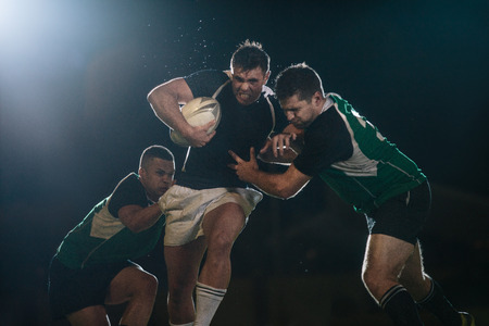 Rugby player in possession of the ball and attempting to advance. Rugby players blocking and tackling opponent player to get the ball. Banco de Imagens