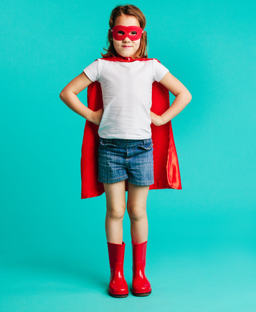 Portrait of cute caucasian girl child in red superhero costume and mask. Small girl in red cape, gumboot and eye mask with hands on hips over blue background.