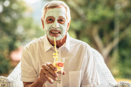 Funny elderly man with clay mask on face drinking juice. Retired senior man at home taking care of his skin at old age. Stock Photo
