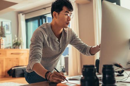 Fotograf edytuje przykładowe sesje na swoim komputerze w studio. Mężczyzna pracujący na komputerze w studiu fotograficznym.
