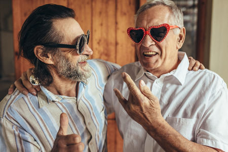 Happy old men wearing funny sunglasses making funky gestures. Stock Photo