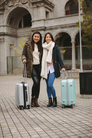 Tourist women standing in street holding their luggage bags.