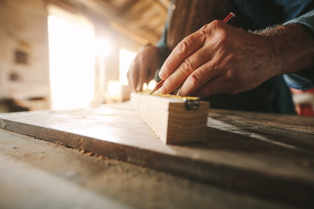 Close up of hands of senior carpenter doing some markings on wooden bar with measuring tape and pencil. Stock Photo