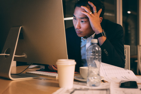 Entrepreneur looking tensed while working late in office.