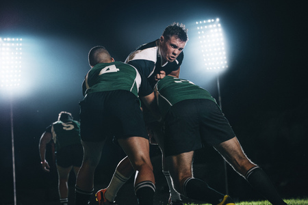 Rugby players fighting for the ball during the night game. Rugby player tackled opponent team players in match. Stock Photo