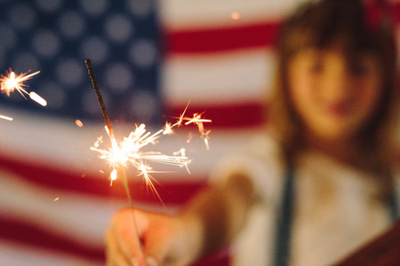 Kid celebrating american independence by burning fire sparkles. Stok Fotoğraf