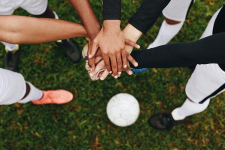 Bovenaanzicht van handen van spelers die over elkaar zijn geplaatst en in een wirwar staan. Spelers die in een wirwar staan en hun handen in het midden samenvoegen met een voetbal op de grond. Stockfoto