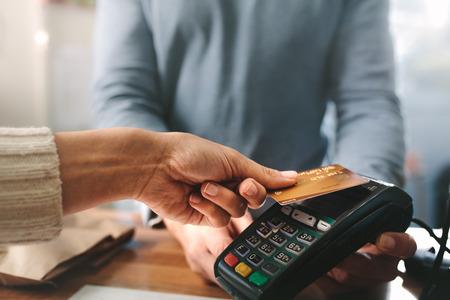 Apotheker die creditcard accepteert door contactloze betaling. Vrouw die producten in de apotheek koopt. Apotheker handen opladen met creditcardlezer.