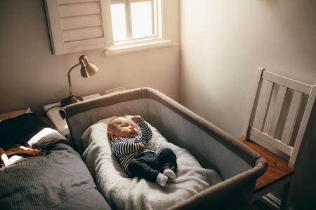 Baby sleeping in a bedside bassinet in bedroom. Archivio Fotografico