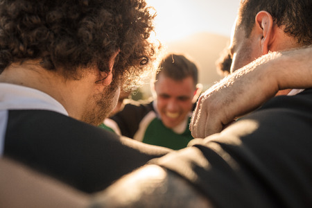 Close up of rugby players standing in a huddle. Stock Photo