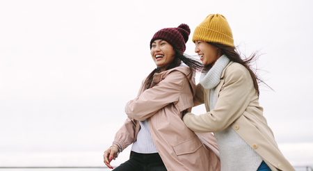 Happy asian woman in winter wear standing outdoors on a cold winter morning.