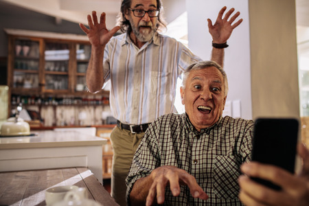 Retired men making funny faces while taking selfie using their smartphone. Crazy old male friends taking self portrait indoors. 스톡 콘텐츠