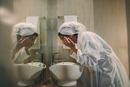 Side view of african woman in bathrobe washing her face in bathroom sink and looking into the mirror.