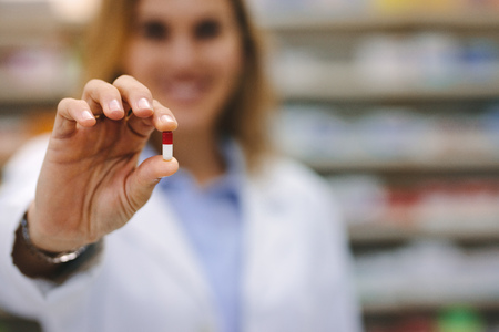 Hand of female pharmacist holding a medicine capsule.