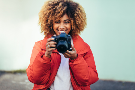 Portrait of a cheerful afro american woman holding a dslr camera. Stock Photo