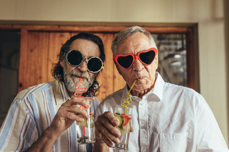 Senior men wearing funny sunglasses drinking juice with straw. Elderly friends with crazy eyewear having juice indoors.