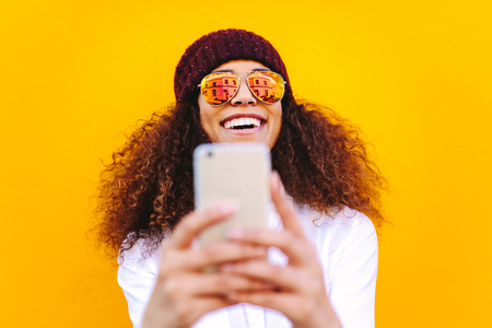 Stylish african woman using mobile phone to taking selfie on yellow wall.