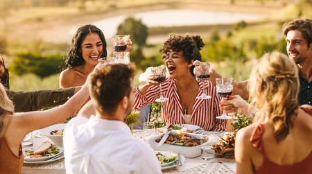 Group of cheerful friends having wine at dinner party. Multi-ethnic people having a get together outdoors. Banco de Imagens