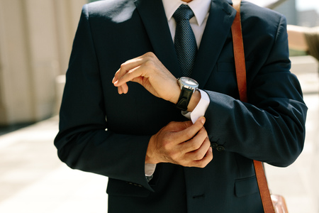 Businessman buttoning his shirt shelves walking outdoors. Close up of business professional buttoning up his shirt sleeves.