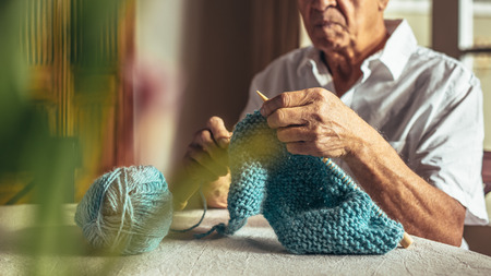 Close up of old man hands knitting with needles and wool yarn. Retired man knitting at home.